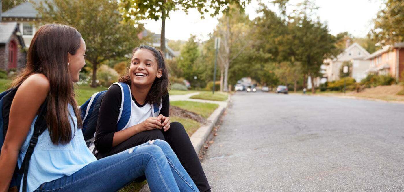 Girls talking on side walk